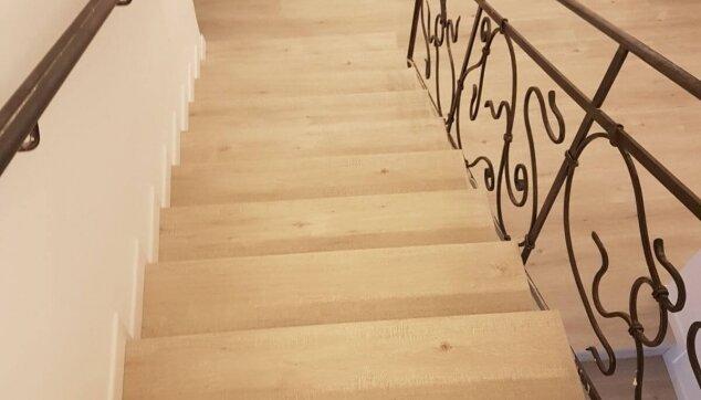 מדרגות-בפרקט-למינציה-מצד-אחד-קיר-עם-פנל-לבן-ומהצד-השני-פיניש-גמר-מושלם-ליד-המעקה
