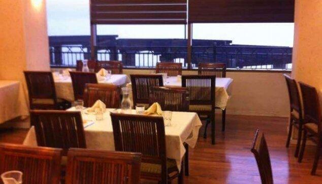 פרקט למינציה בחדר אוכל של בית מלון ווילונות לייט סקרין לשליטה באור ובחום