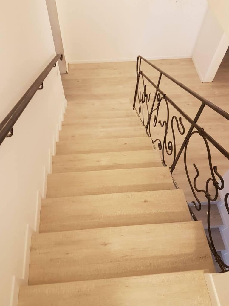 מדרגות בפרקט למינציה מצד אחד קיר עם פנל לבן ומהצד השני פיניש גמר מושלם ליד המעקה