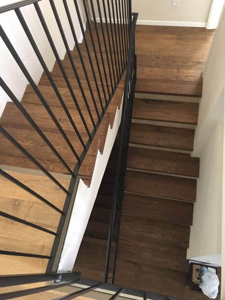 פרקט עץ במדרגות אשר מתחבר לפרקט למינציה בקומת חדרים